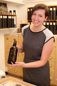 University of Victoria Archaeology professor Katherine Cook holds an Australian beer bottle recovered from a Victoria construction site. The bottle was featured in Bridging Victoria: Stories from the Archaeological Past.   one-off show featured artifacts recovered from construction sites in the city.