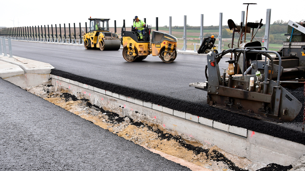 Compactors at work on the asphalt overlay on the Satzengraben bridge in Austria. The series of concrete elements beneath the asphalt are visible in the cut-out.
