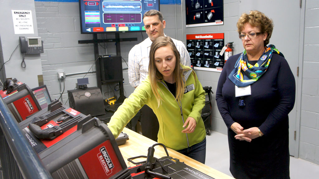 The grand opening for the new Smart Welding Lab at George Brown College features virtual welding equipment where students can practise their skills. Pictured, George Brown College president Anne Sado (right) learns how the machine works before testing it out.
