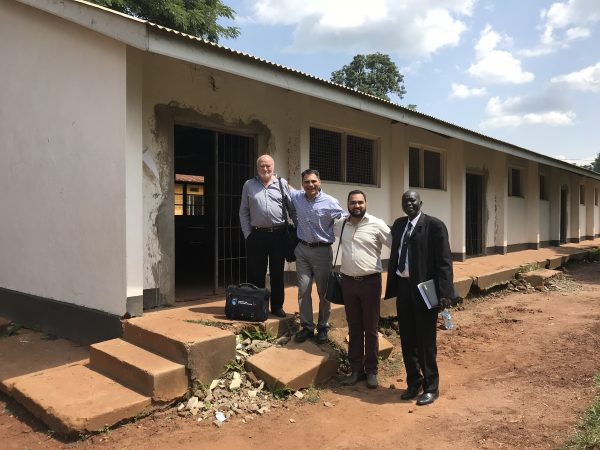 NAIT representatives Dr. Dave Rea, Ignacio Garcia and Dalpreet Virdi stand with Uganda Technical College deputy principal Moses Obong in front of the building that, once refurbished, will house a road construction training program scheduled to take place from 2019 to 2021.