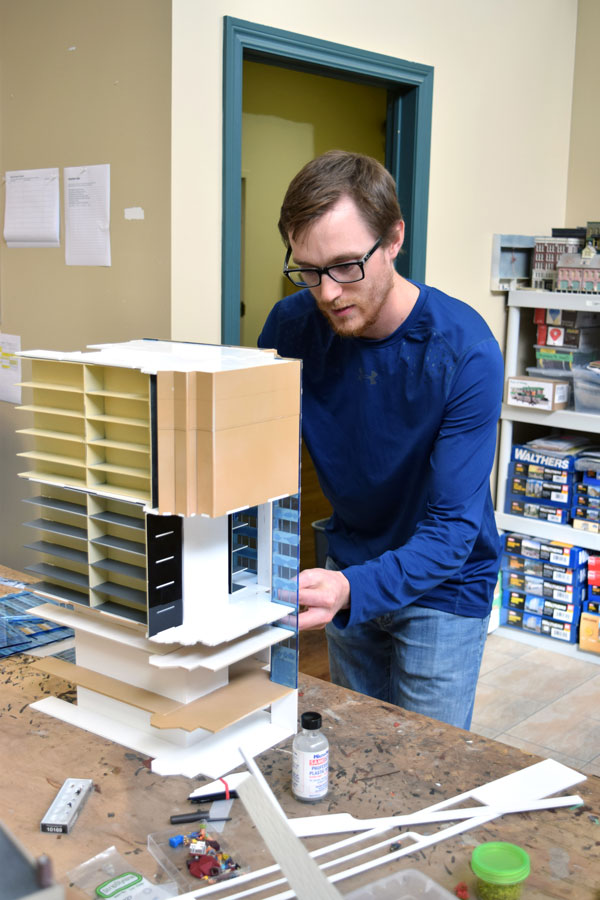 Onsite at the Britannia Road East workshop of Our Home & Miniature Land in Mississauga, modeller Mark Domanski examines a model of the Place du Portage building in Ottawa.