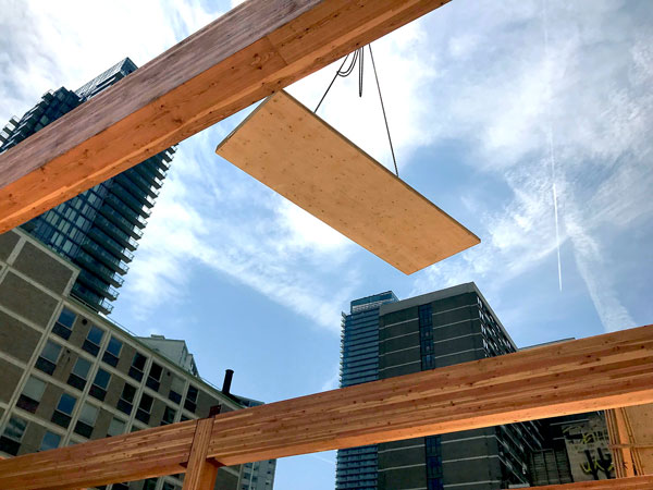 The Timber Systems crew installed 15 to 20, 2.7-metre-by-12.7-metre cross-laminated timber (CLT) panels per day from a truck positioned in a one-lane closure on Charles Street in Toronto. Glulam and CLT products were marshalled at Timber Systems facility in Markham, Ont.