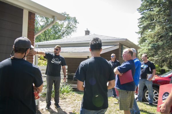 Construction crew members from Build Love, a Saskatchewan volunteer organization, take a look at what they can do for a home renovation.