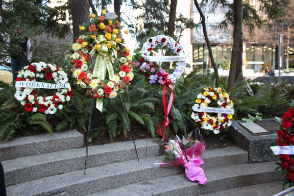 Wreaths from several labour and safety organizations surround the memorial plaque commemorating the lives lost on Jan. 7, 1981.
