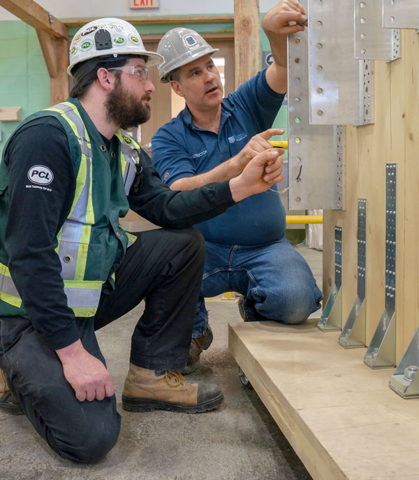 Timber course student Tyler Brayshaw learns the ins and outs of timber construction from course instructor Jason Moreau. The course, put on by the College of Carpenters and Allied Trades, covers timber framing tools and fastening systems as well as methods of installing prefabricated cross-laminated timber walls and ceilings.
