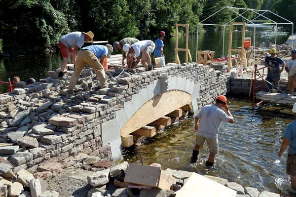 Wallers fill in the voids between the voussoirs with other stones on a bridge over the Tay River in Perth, Ont.