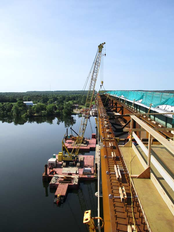 The team working on the Bay of Quinte Skyway Bridge rehabilitation project is using cranes on barges to remove existing structural steel girders and replace them with new ones.