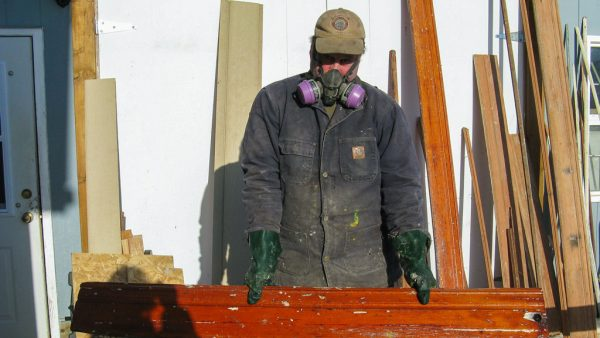 Contractor Jamie Toole dips some of the original woodwork of the Caribou Hotel during renovations. Just this year, as he headed down a hotel staircase, after finishing some drywalling, he heard steps coming up the stairs towards and then past him — but no one was there, he says.