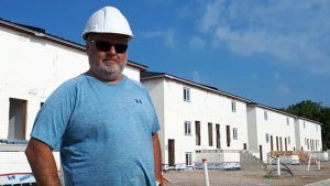 Jim Liovas, president of Liovas Homes, stands in front of a row of new migrant worker apartment blocks in Leamington, Ont. Each two-storey building, on either side of the street, will have six apartments and accommodate 36 workers.
